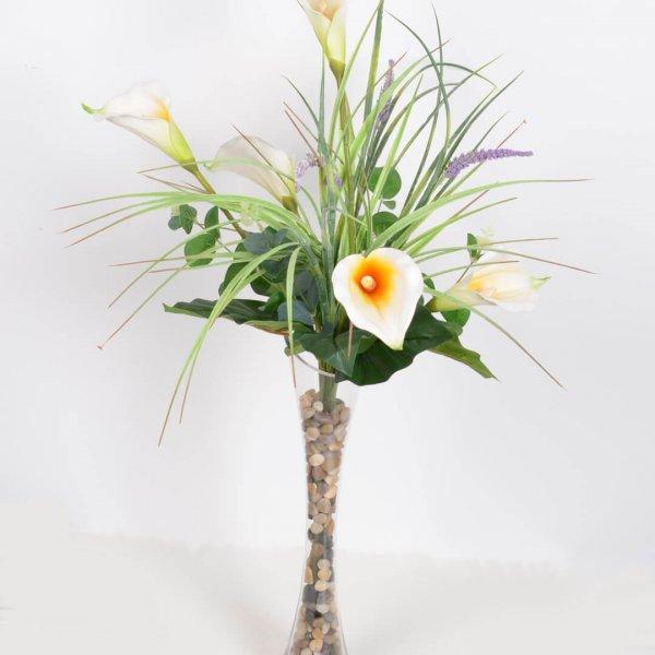 פרחי קאלות בכלי זכוכית גבוה וצר