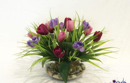 סידור טוליפים ופרחים סגולי בכלי חללית שקוף